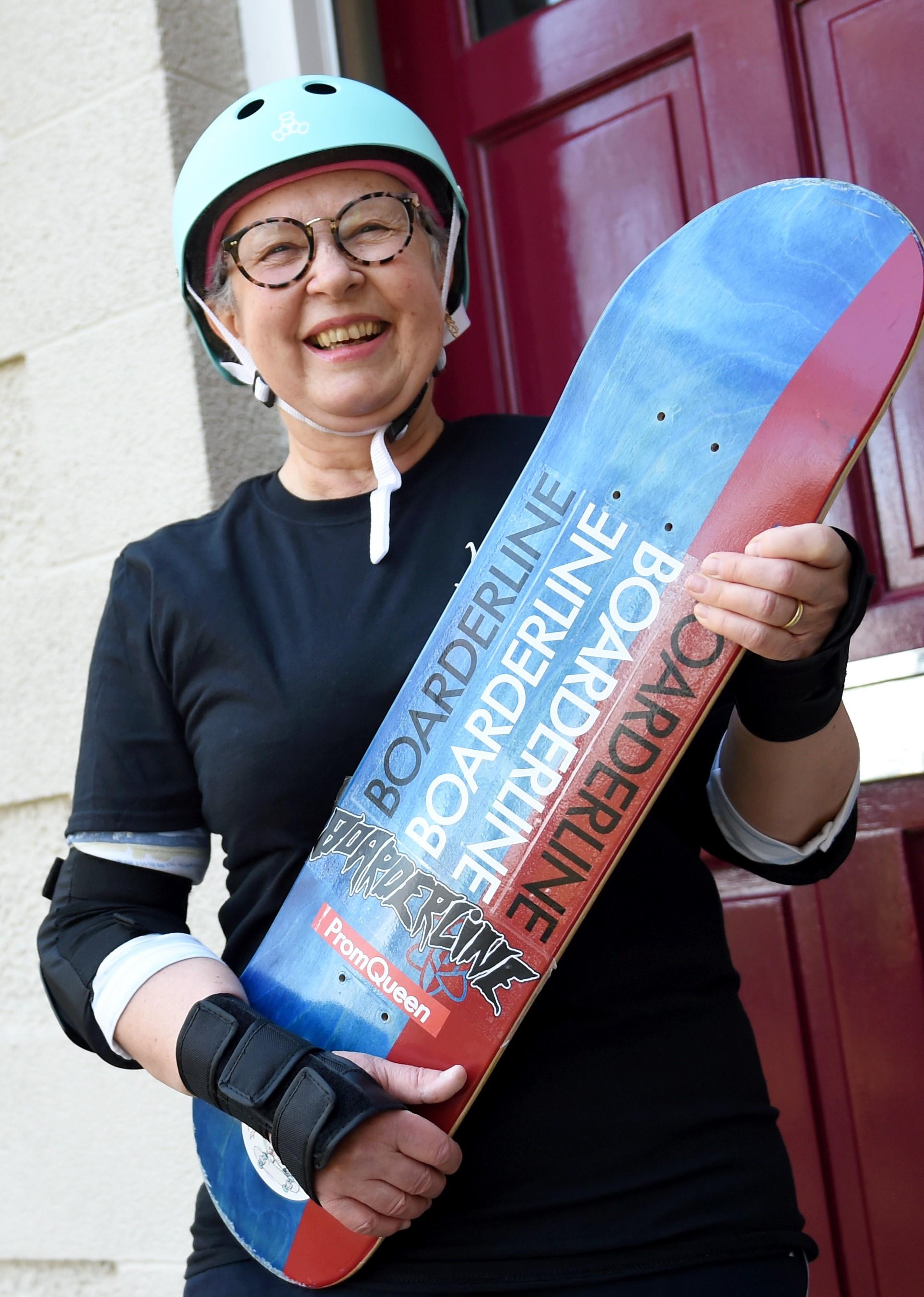 Elain Shalcross holding skateboard at her front door